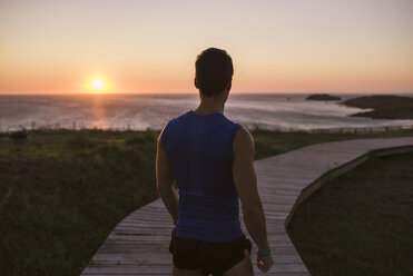Spain, Ferrol, back view of a jogger standing on boardwalk watching sunset - RAEF000482
