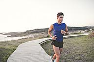 Spain, Ferrol, jogger running on a boardwalk - RAEF000479