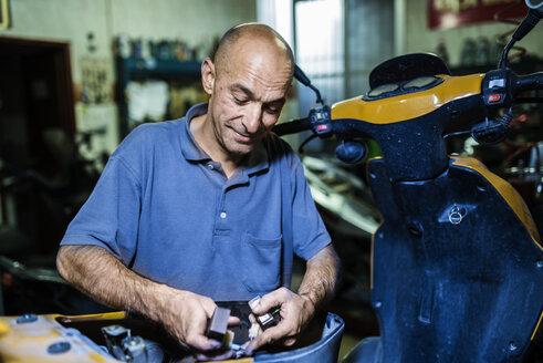 Mechanic working in his motor scooter workshop - JASF000099