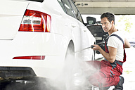 Car cleaning, man cleaning car with high-pressure cleaner - LYF000489