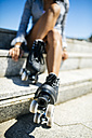 Spain, Gijon, teenage girl with roller skates sitting on stairs - MGOF001000