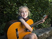 Spain, girl playing spanish guitar outdoors - RAEF000476