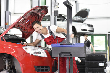 Car mechanic working in repair garage, setting car headlights - LY000517