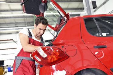 Car mechanic working in repair garage, repairing rear light - LYF000521