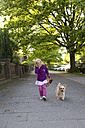Portrait of laughing little girl walking with her dog - JFEF000697
