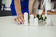 Close-up of hand holding high-rise building model next to wind turbine model on conference table - MFF002148