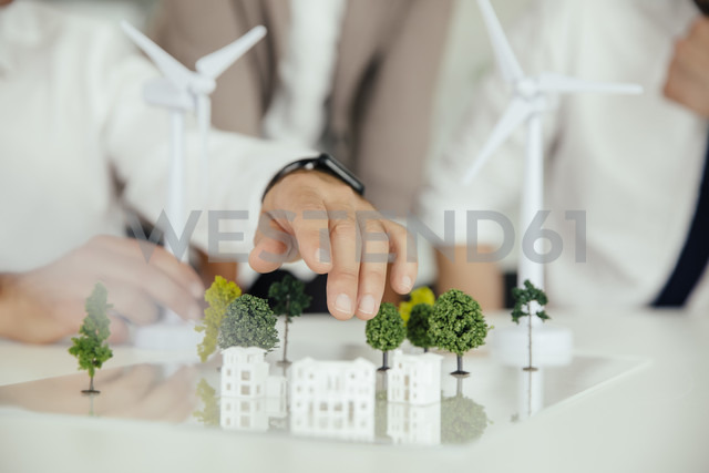 Close-up of business people wind turbine model and houses on conference table - MFF002154