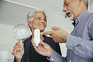 Businesswoman and businessman comparing regular and energy-saving lightbulb - MFF002160