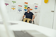 Smiling man in wheelchair in modern office - MFF002209