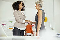 Female boss shaking hands with employee in office - MFF002171