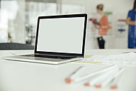 Laptop on desk in office with employees in background - MFF002174