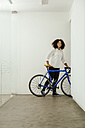 Smiling young woman with bicycle in office - MFF002210