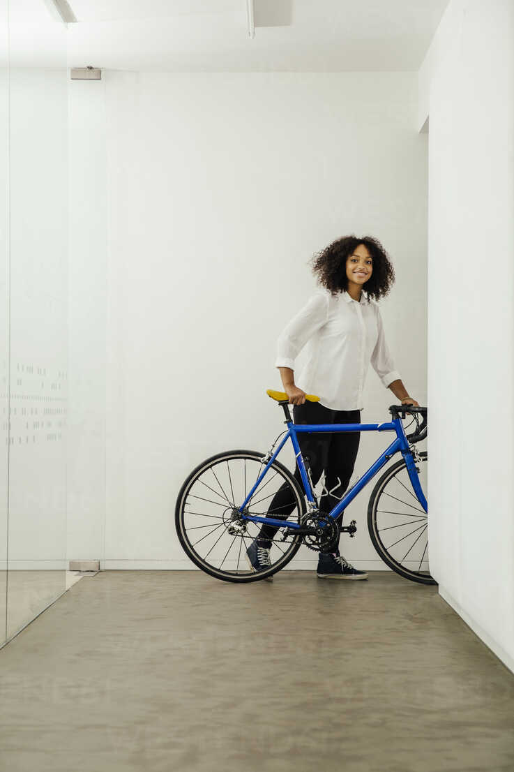 Smiling young woman with bicycle in office - MFF002210 - Mareen Fischinger/Westend61