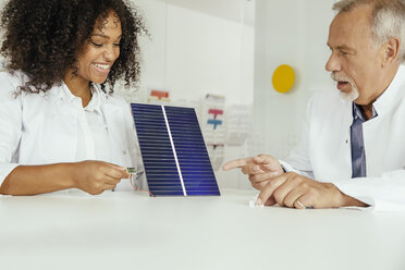 Two scientists talking about a solar panel with voltmeter in lab - MFF002201
