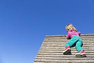 Blond little girl climbing on wooden hut - JFEF000698