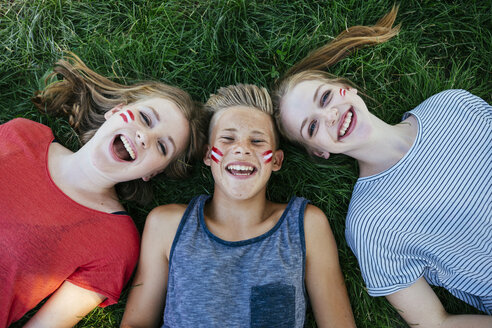 Austria, three teenagers with national colors painted on their cheeks lying on a meadow - AIF000010