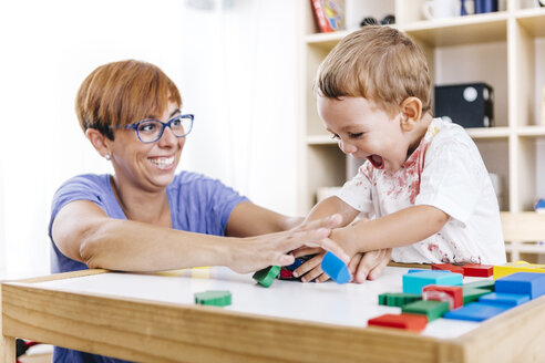 Portrait of little boy and his mother playing together with building bricks - JRFF000057