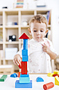 Little boy built a tower with blue and red building bricks - JRFF000061
