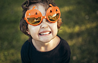 Portrait of little girl wearing halloween glasses shaped like pumpkins pouting mouth - MGOF000667