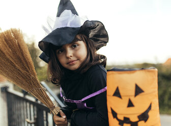 Portrait of little girl masquerade as a witch with halloween lantern and broom - MGOF000672
