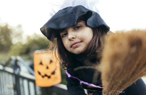 Portrait of little girl masquerade as a witch with halloween lantern and broom - MGOF000673