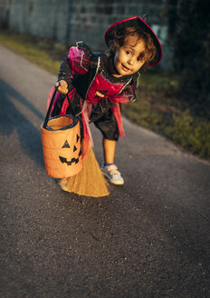 Portrait of little girl masquerade as a witch with halloween lantern and broom - MGOF000674