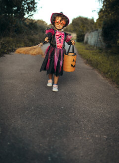 Little girl masquerade as a witch with halloween lantern and broom - MGOF000676
