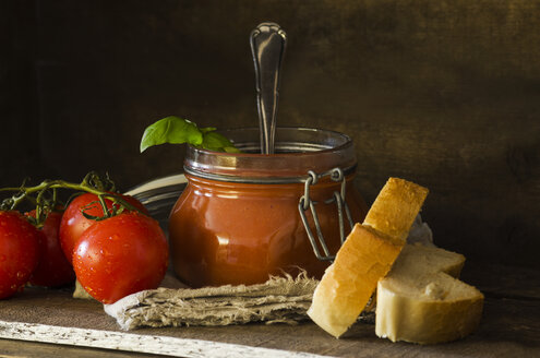 Fresh tomato soup with basil in preserving jar, tomatoes, white bread on wood - ODF001317