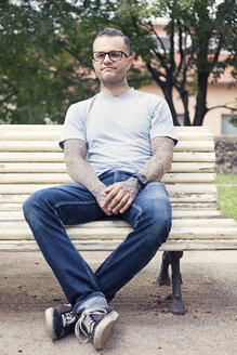 Tattooed man sitting on a park bench - XCF000017