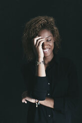 Portrait of smiling woman with closed eyes and hand on her face in front of black background - EBSF000904
