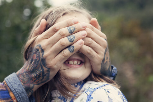 Man's tattooed hands covering eyes of his daughter - XCF000014