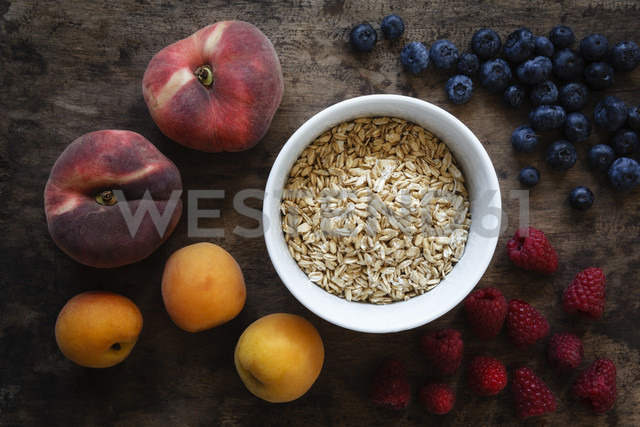 Bowl of oak flakes and different fruits on dark wood - EVG002227