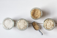 Glasses of oat grains, flakes and bran on white ground - EVGF002230