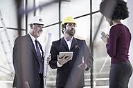Two businessmen wearing hard hats talking to woman - ZEF008366