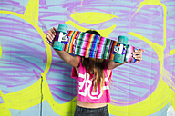 Teenage girl standing in front of wall with graffiti hiding behind colorful skateboard - GEMF000361