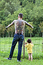 Back view of a tattooed man with his little son standing in front of a fence - XCF000021
