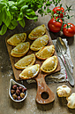Stuffed pastry with black olives, tomatoes and basil on wooden board - ODF001322