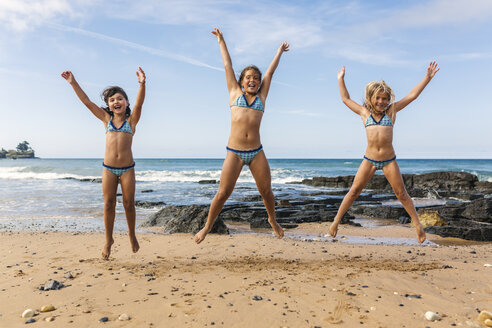 Spain, Colunga, three girls jumping in the air on the beach - MGOF000714