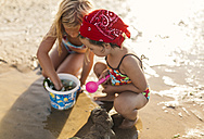 Two little girls playing together on the beach - MGOF000728