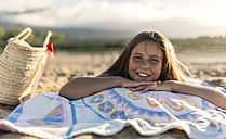 Portrait of smiling girl lying on a blanket on the beach - MGOF000730