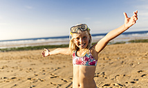 Spain, Colunga, portrait of smiling blond little girl with diving mask and arms outstretched on the beach - MGOF000732