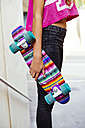 Young girl holding a colorful skateboard - GEMF000367