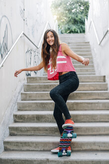 Happy teenage girl with skateboard on stairs - GEMF000373