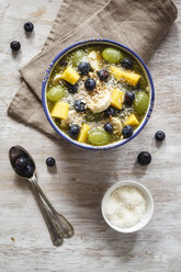 Bowl of green smoothie and fruits sprinkled with coconut flakes - EVGF002254