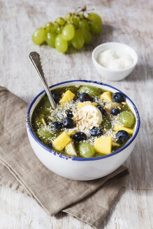 Bowl of green smoothie and fruits sprinkled with coconut flakes - EVGF002256