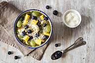Bowl of green smoothie and fruits sprinkled with coconut flakes - EVGF002257