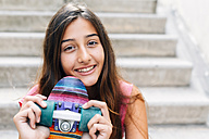 Portrait of smiling teenage girl with colorful skateboard sitting on stairs - GEMF000376