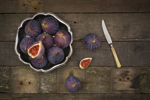 Bowl of figs and a knife on dark wood - LVF003832