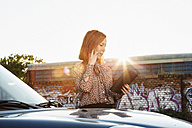 Businesswoman with file standing behind parked car telephoning at backlight - TAM000311