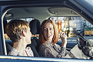Two female friends sitting in their car talking together - TAM000314